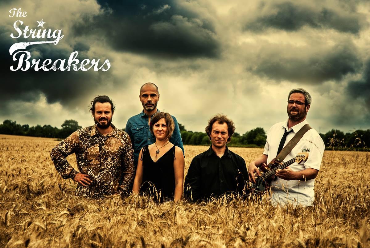 Les membres du groupe The String Breakers dans un champ, ils viennent jouer au café-concert Le Centre à Saint Nazaire.